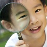 Young Asian boy with magnifying glass in front of his eye